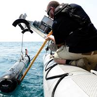A civilian contractor steadies a M18 Mod 2 Kingfish Unmanned Underwater Vehicle (UUV) as it is lifted with a crane onto the deck of an 11-meter rigid-hull inflatable boat. The Kingfish uses side scan sonar to search and discover objects of interest. This marks the first time these UUVs have been added to mine countermeasure operations in the U.S. 5th Fleet area of responsibility.  (U.S. Navy photo by Mass Communication Specialist 2nd Class Blake Midnight/Released)