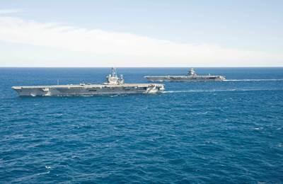 The aircraft carrier USS Enterprise (CVN 65) passes the aircraft carrier USS Harry S. Truman (CVN 75) in the Atlantic Ocean. (U.S. Navy photo by Naval Aircrewman (Tactical Helicopter) 3rd Class Matt Ballard/Released)
