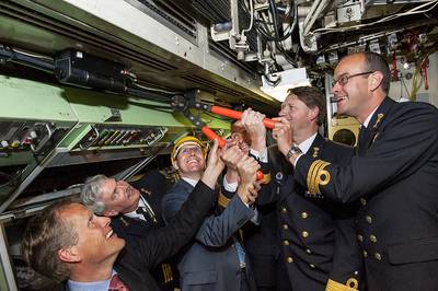 'Commodore Hans Lodder and Sytze Voulon of Imtech Marine Netherlands are cutting the cable in de commandcenter of Zr.MS. Zeeleeuw. From left Henk Jan Vink (TNO Director defence research), Commander Jouke Spoelstra, Sytze Voulon (Managing Director Imtech Marine Netherlands), Captain Marc lsensohn, Commodore Hans Lodder and Commander Danny van den Bosch. Photo: Ministry of Defence.'