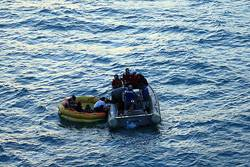 Sailors from the guided-missile destroyer USS John S. McCain (DDG 56) pull sailors from the Republic of Korea (ROK) commercial fishing boat M/V Je 2 Bong Ho into a Rigid Hull Inflatable Boat. The ROK sailors abandoned their vessel after it caught fire. U.S. Navy photo by Chief Intelligence Specialist Thomas Fischer