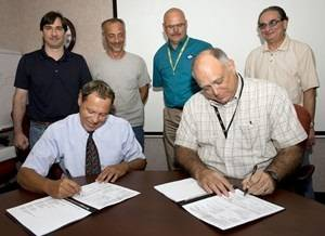 Seated, l-r: Marty Capalbo, configuration manager for Supervisor of Shipbuilding (SUPSHIP) Gulf Coast, (left) and John Broderick, Ingalls' systems integration manager, (right) sign transferring paperwork at a ceremony Wednesday. Standing, l-r: Jason Frioux, PVLS program manager, Ingalls; Chip Stargardt, Quality Assurance, SUPSHIP; D.R. Clark, PVLS ship superintendent, Ingalls; and Zachery Michini, production controller, SUPSHIP. Photo by Steve Blount