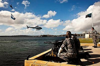 The Royal Australian Navy's Three Pound Saluting Gun Battery prepares to fire across Sydney Harbour as a Squirrel Helicopter decorated with International Fleet Review decals hovers off Garden Island Naval Base as a Seahawk helicopter flying a giant International Fleet Review Flag flys past.