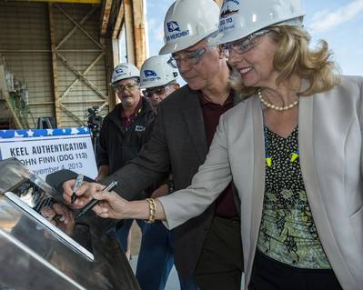 Laura Stavridis, the ship's sponsor, (right) and Bob Merchent, Ingalls vice president of U.S. Coast Guard and surface combatant programs, (second from right) mark their initials on the keel plate for the destroyer John Finn (DDG 113). Also pictured are (left to right) George Nungesser, Ingalls' DDG 51 program manager, and Ingalls Shipbuilding President Irwin F. Edenzon. Photo: Lance Davis