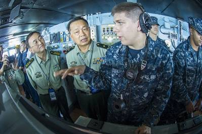 Seaman Alex Snyder, right, explains the functions of the helm on the navigation bridge of the aircraft carrier USS George Washington to Maj. Gen. Chen Weizhan, deputy commander of the People's Liberation Army, Hong Kong Garrison, center, and Col. Li Jiandang, Hong Kong Garrison liaison officer during a distinguished visitor embark. (U.S. Navy photo by Ricardo R. Guzman)