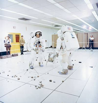 Members of the Apollo 12 lunar landing mission, Charles Conrad Jr. (facing camera) simulates picking up samples, and aAlan L. Bean simulates photographic lunar rock sample documentation, as they participate in lunar surface extravehicular activity (EVA) simulations in the Flight Crew Training Building at the Kennedy Space Center (KSC).  (Photo: Review of U.S. Human Space Flight Plans Committee)
