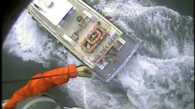 A Coast Guard rescue swimmer is lowered to the Osprey II and a man suffering from chest pains is hoisted back up Saturday near Port Mansfield, Texas. U.S. Coast Guard video by Air Station Corpus Christi.