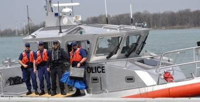 Members of Coast Guard Station Belle Isle in Detroit, and a member of the Royal Canadian Mounted Police pose for a photo on a 45-foot patrol boat after conducting a joint patrol in Lake Erie, May 8, 2014. (USCG Guard photo courtesy of Coast Guard Sector Detroit)