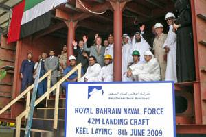 Staff Colonel Hasan Ahmed Mohammed, Head of the Planning Department, Royal Bahrain Naval Force and ADSB CEO Bill Saltzer with ADSB management and employees inside the first hull block constructed for the landing craft.