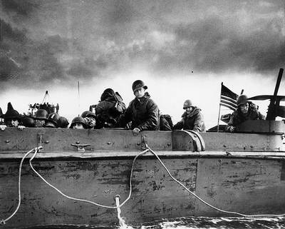 """Troops and crewmen aboard a Coast Guard manned LCVP as it approaches a Normandy beach on """"D-Day"""", June 6, 1944. (Photograph from the U.S. Coast Guard Collection in the U.S. National Archives.)"""