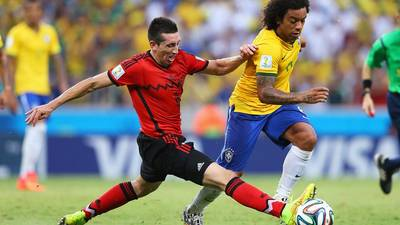 Marcelo of Brazil is challenged by Hector Herrera of Mexico (Photo courtesy of FIFA)