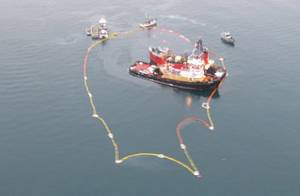 The Valdez Star begins preparation to lighter the tug Pathfinder south of Busby Island and is surrounded by containment boom with spill responders staged nearby Dec. 25, 2009. The Pathfinder crew had completed an ice survey and was heading back to its port in Valdez when the vessel struck the Bligh reef Dec. 23, 2009. (Photo courtesy of John Engles)