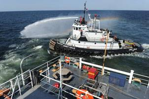 Commercial tugboat Janet Colle pressure washes the exterior of USCGC Harry Claiborne (WLM 561) of residual oil after an oil clean up mission. Claiborne is equipped with a Vessel of Opportunity Skimming System (VOSS) to help remove oil from the ocean surface. (U.S. Navy photo by Mass Communication Specialist 2nd Class (AW/SW) Jonathen E. Davis)
