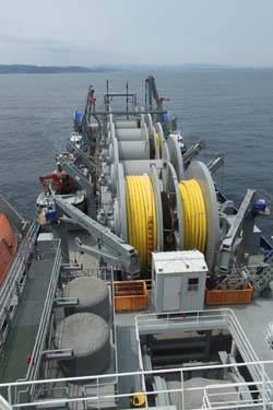 Offshore petroleum distribution system ship MV Vice Adm. K.R. Wheeler deploys yellow, flexible pipe to the seabed off the coast of Pohang, Republic of Korea, June 23. (U.S. Navy photo by Ed Baxter, Sealift Logistics Command Far East)