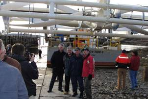 Coast Guard Sector Northern New England's commander, Capt. James McPherson (3rd from left), poses with members of the Ocean Renewable Power Company (ORPC) in front of the barge Energy Tide 2 March 2, 2010. The Energy Tide 2 will be used to generate green, renewable energy to be used at Coast Guard Station Eastport during a testing phase for ORPC. Coast Guard photo by Petty Officer 1st Class Rich Cherkauer.
