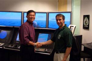 Mark Broster of ECDIS Ltd shaking hands with LTC Terence Ho of the Republic of Singapore Navy. Photo courtesy ECDIS