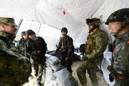 Coast Guard Petty Officer 2nd Class Spencer Filzen (second from right), of Port Security Unit (PSU) 313 of Everett, Wash., talks with marines from the Republic of Korea while standing a joint, security watch at the Joint Operations Center during a Combined Joint Logistics Over-the-Shore Exercise (CJLOTS), April 20, 2013. This is the first time since 2006 that a Coast Guard PSU has participated in the Korean Theater of Operations (KTO). (U.S. Coast Guard photo by Petty Officer 2nd Class Etta Smit