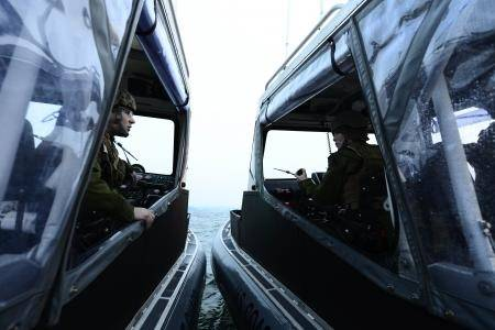U.S. Coast Guard Petty Officer 1st Class Jordan Gere (left) and Petty Officer 2nd Class Carla Galland (right), both of Coast Guard Port Security Unit (PSU) 313, from Everett, Wash., talk during a security patrol off the coast of Dogu Beach in support of exercise Foal Eagle, April 21, 2013. PSU 313 along with Republic of Korea military forces, provided 24-hour water-side and shore-side force protection during Foal Eagle, a Combined/Joint Logistics Over-the-Shore Exercise (C/JLOTS). (U.S. Coast Gu