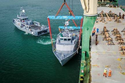 U.S. merchant mariners and stevedores carefully lift and secure watercraft in preparation for its voyage across the Pacific Ocean.