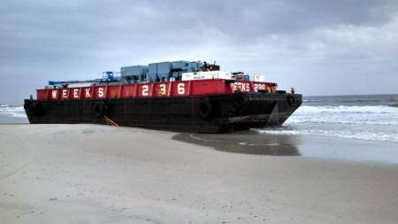Towing vessel Pushy had lost control of a 125-foot deck barge it was towing following an interaction with a large swell off of Atlantic Beach, N.Y. After the towing vessel and deck barge separated, the vessel sank and the barge was pushed up onto the beach at Silver Point County Park. U.S. Coast Guard photo.