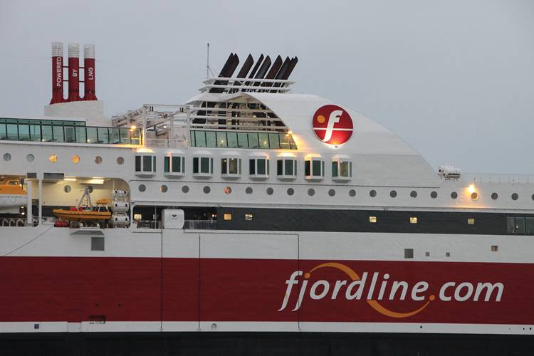"""The characteristic, red painted, gas vent lines, featuring """"Powered by LNG"""" on top of the vessel."""