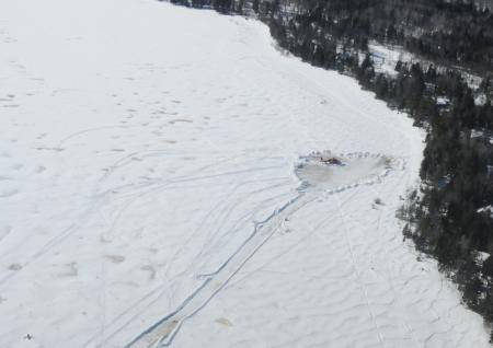 A Dolphin helicopter from Coast Guard Air Station Traverse City, Mich., sits on the snow-packed shore of Washington Island, Wis., as preparations are made to recover the aircraft, March 3, 2014. (USCG photo)