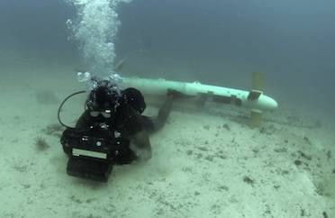"""A diver tests underwater imaging system in the Arabian Sea, after an airborne platform """"saw"""" this mine through the water. """"The emphasis here,"""" says Dr. Jason Jolliff, an NRL oceanographer who forecasts ocean optics, """"is on developing models of the ocean environment to help the naval warfighter."""" (Photo: U.S. Navy)"""