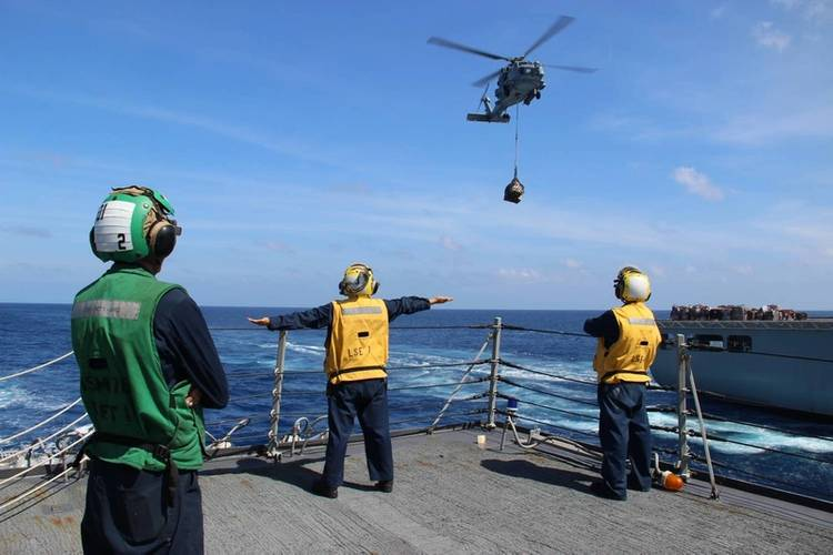 U.S. Navy Sailors use hand signals while directing helicopter operations aboard the Arleigh Burke-class guided-missile destroyer USS Kidd (DDG 100). Kidd is conducting search and rescue operations for the missing Malaysian Airlines flight MH370. (U.S. Navy photo by Karmowska-Brooks)