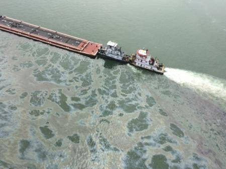 A barge loaded with marine fuel oil sits partially submerged in the Houston Ship Channel, March 22, 2014.
