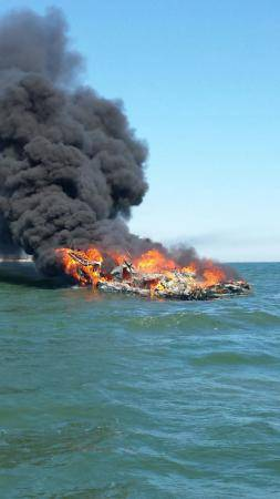 The Coast Guard rescued three people from the water after their boat caught fire near Shinnecock, N.Y. The fire engulfed the 36-foot cabin cruiser and the three people abandoned the vessel into the water to swim to their deployed life raft. (U.S. Coast Guard photo by Adam Long)
