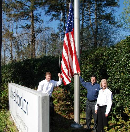 Martin Magill, Senior Vice President; Pierre Tanguay, VP Supply Chain; and Angelyn Gill, Health Safety and Environmental Coordinator, raising the flag at Wheelabrator, LaGrange