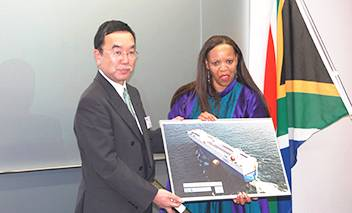 """A Panel of MOL's cutting-edge hybrid car carrier """"Emerald Ace"""" ,which carried eight mobile library vehicles last year, was presented to South African Ambassador in Japan Her Excellency Mohau Pheko by MOL Senior Managing Executive Officer Takashi Kurauchi."""