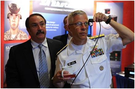 Rear Adm. Matthew Klunder, chief of naval research, tries out a low cost augmented reality head mounted display with SA Photonics general manager, Michael Browne, while touring the exhibit hall at the 2014 Navy Opportunity Forum. The forum is designed to facilitate interaction between small business and members of the acquisition community, lead system integrators, and first and second tier suppliers. (U.S. Navy photo by John F. Williams)
