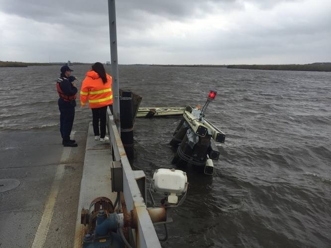 A Coast Guardsman from the Marine Safety Unit Port Arthur stands at the edge of Black Bayou Bridge observing a damaged fender after it was hit by a boat that lost steering March 7, 2016. (U.S. Coast Guard photo by Jennifer Andrew)